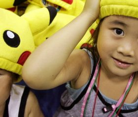 Ami Kobayashi (R) and her younger brother Akio put on Pokemon caps during Pokemon Festa 2005 in Yoko..